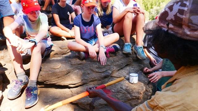Kinder schauen dem Aborigine Hilton gespannt zu.