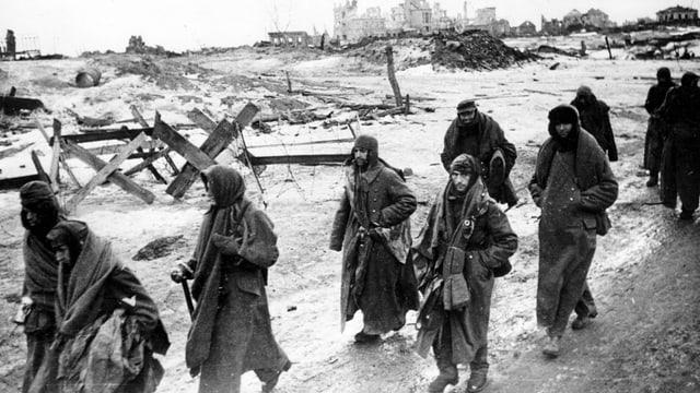 Russische Soldaten verlassen zu Fuss eine zerstörte Stadt.