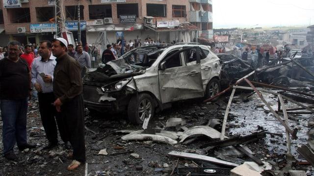 Zerstörtes Auto und Trümmer liegen auf der Strasse. Zahlreiche Männer stehen um den Schauplatz herum.
