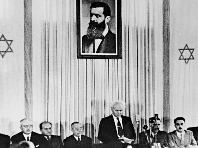 An einem langen Tisch sitzen Männer, dazwischen steht David Ben-Gurion, der erste Premierminister. Über ihm ein Bild von Theodor Herzl.
