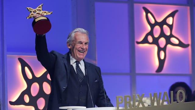 Pepe Lienhard lacht und hält den Ehren Prix Walo hoch.