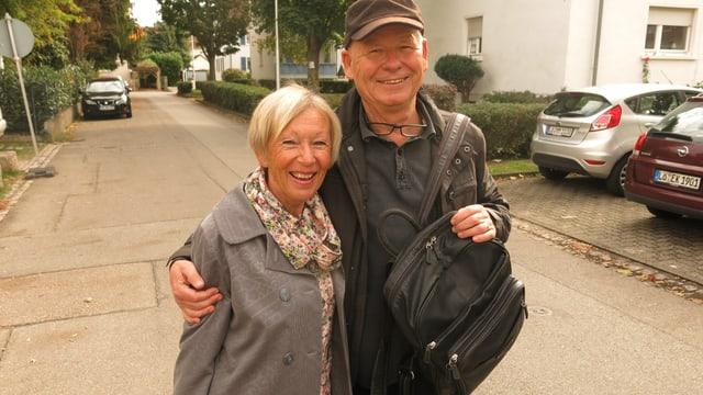 Ein Rentnerehepaar steht auf einer Strasse. Er trägt einen Rucksack. BEide schauen zur Kamera.
