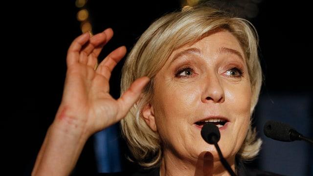 Marine Le Pen vor einem Mikrofon gestikuliert mit der rechten Hand