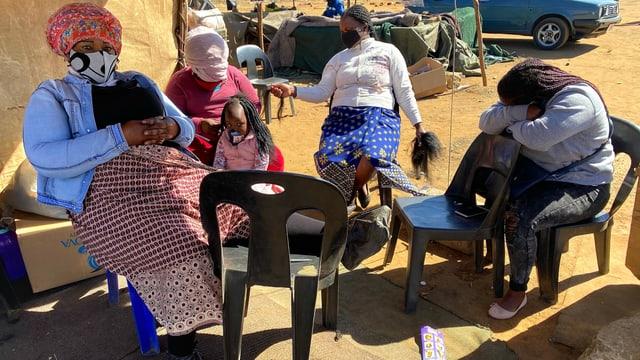 Fünf Frauen sitzen im Kreis an einer Wand in Südafrika.