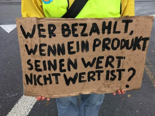 """Schild mit der Aufschrift: """"Wer bezahlt, wenn ein Produkt seinen Wert nicht wert ist?"""""""