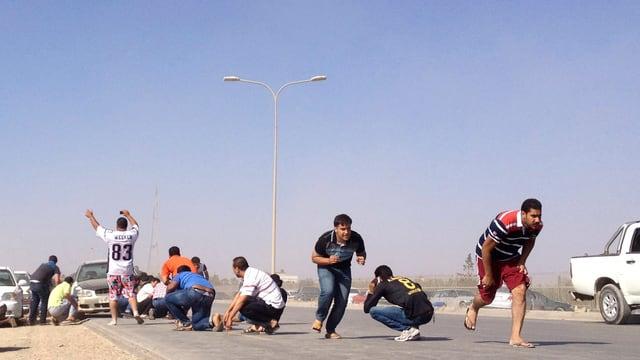 Männer rennen oder kauern auf dem Boden