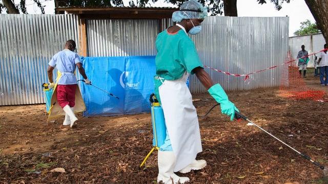 Personen in Sicherheitskleidung mit Desinfektionsspritzen