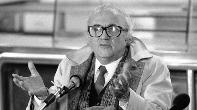 Federico Fellini steht gestikulierend vor einem Mikrofon.