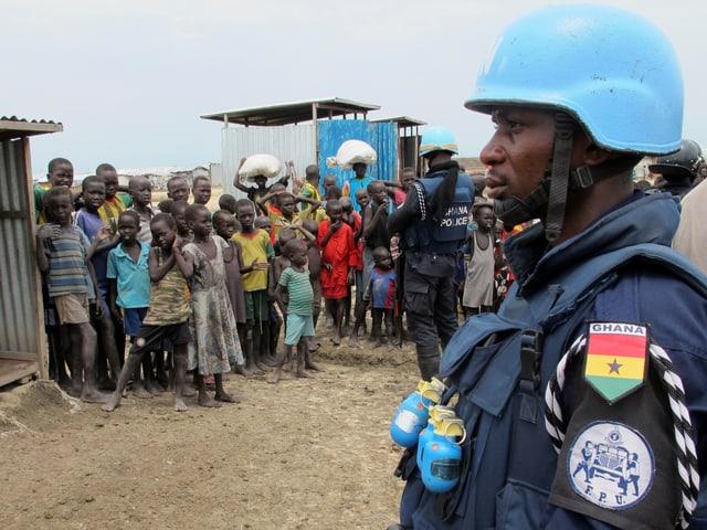 Ein Blauhelmsoldat der UNO und Flüchtlingskinder in einem Dorf im Südsudan.