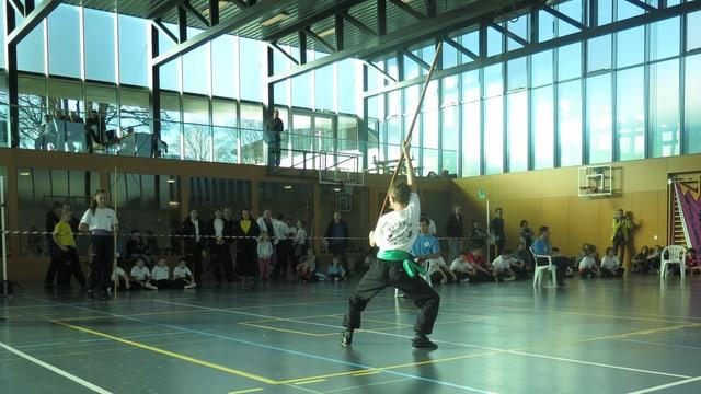 Ein Kind macht Kung Fu mit einem Stock