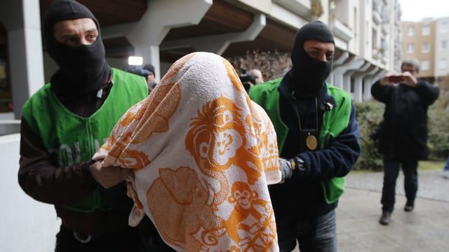 Zwei vermummte Polizisten führen einen Verdächtoigen weg, dessen Kopf mit einem Handtuch bedeckt ist.