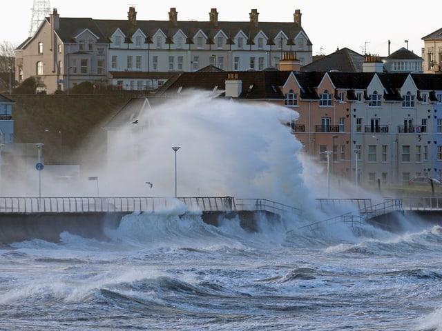Hohe Wellen überfluten Küstenpromenade eines irischen Städtchens.