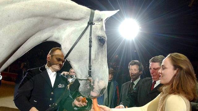 Ein weisses Pferd frisst Rüebli aus den Händen einer Frau, daneben fünf Männer.