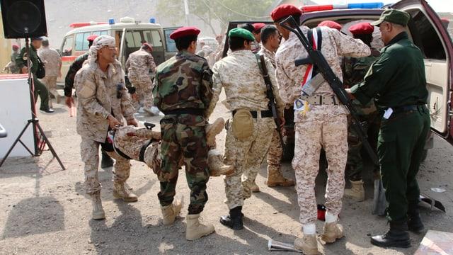 Soldaten tragen verwundeten Kollegen in Rettungswagen.