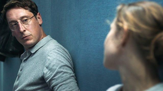 Ein Mann mit Brille schaut eine Frau an, sie beide lehnen an einer Wand.