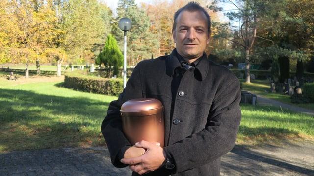 Mann mit Urne im Arm.