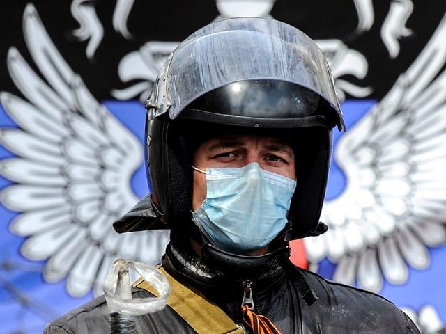 Maskierter Mann mit Sturzhelm.