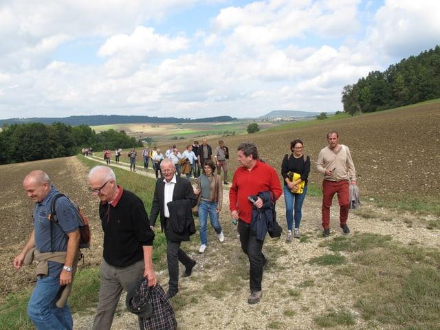 Die Kantonsräte wandern auf einem Feldweg und reden miteinander.