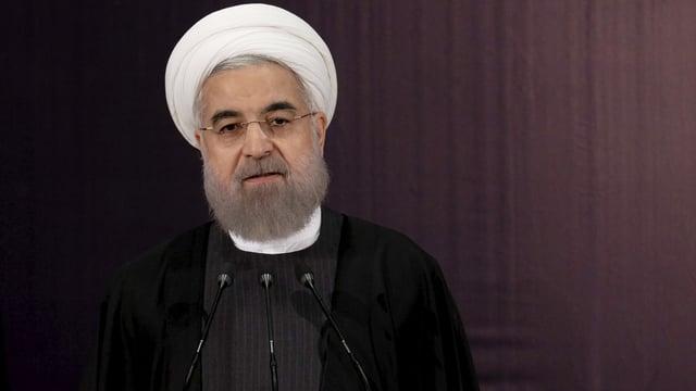 Portrait von Irans Präsident Rohani mit weissem Turban vor dunklem Hintergrund. Er spricht in Mikrofone.