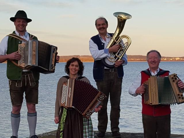 Quartett vor See mit Instrumenten und in Tracht.