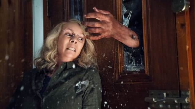 Frau an Tür und Arm durch gebrochenes Fenster in der Tür.