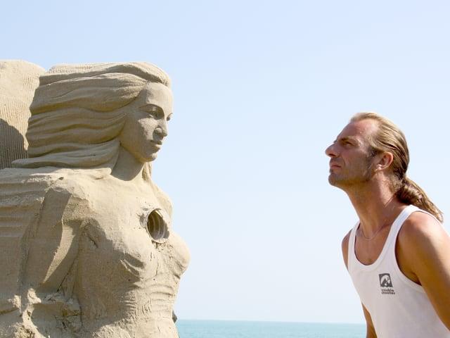 Ein Mann steht einer Sandskulptur gegenüber und schaut sie an.