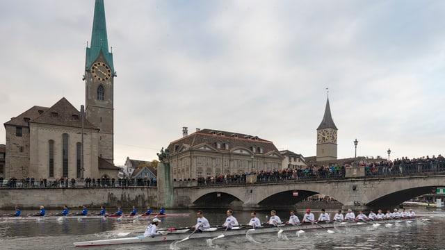Zwei Ruderboote fahren parallel auf der Limmat, im Hintergrund eine Brücke vollgestopft mit Menschen.