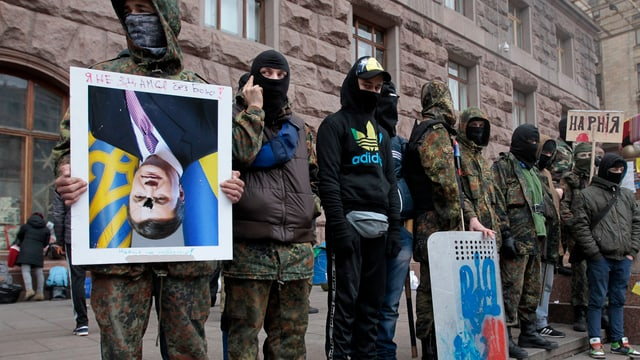 Vermummte Demonstranten vor dem Rathaus in Kiew, einer hält ein Portrait des Präsidenten verkehrt herum.