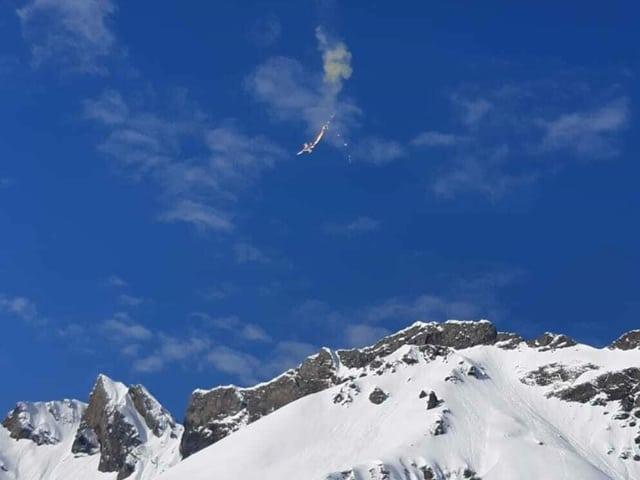 Der Absturz der F5 Tiger Maschine auf der Melchsee-Frutt. Flammen, Rauch und der Fallschirm des Piloten sind sichtbar.