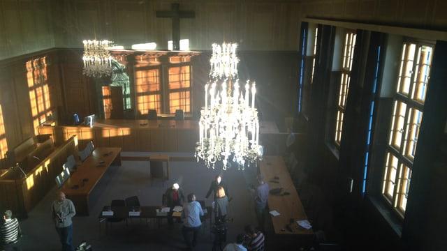Grosser Saal mit Kronleuchter, Kreuz an der Wand, ein paar Journalisten, die herumstehen.