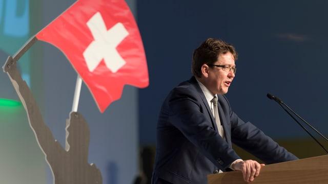 Albert Rösti an einem Rednerpult von der Seite. Am Rand ist eine Figur mit einer Schweizer-Fahne.