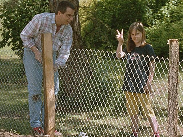 Ein Mann hält einen Holzpflock auf einer Wiese, daran ist ein Gitter befestigt. Daneben steht ein junges Mädchen und blickt in die Kamera.