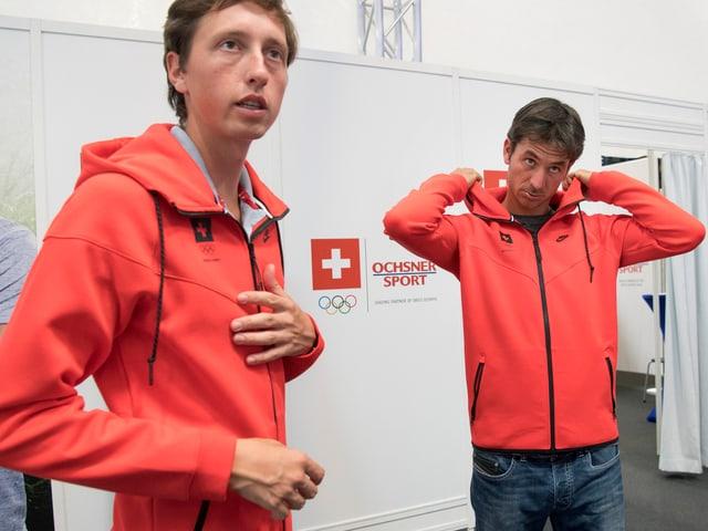 Martin Fuchs und Steve Guerdat ziehen sich eine Jacke an.