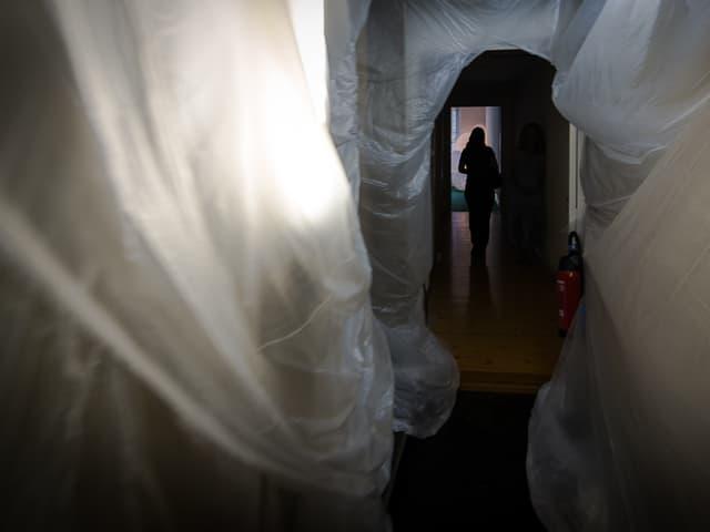 Eine Frau geht durch einen Gang, der mit Plastik ausgekleidet ist.