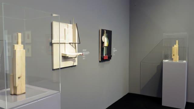 Ausstellungsraum: Zwei Plastiken auf Säulen, zwei Reliefs an der Wand.