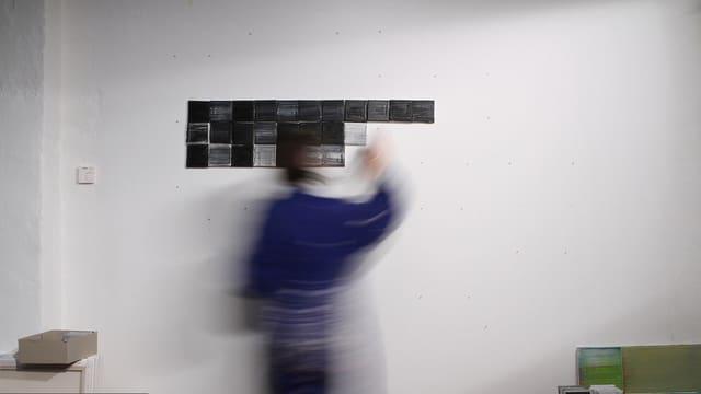 Ein Mann, der nur verschwommen zu sehen ist, hängt schwarze Quadrate nebeneinander an eine Wand.