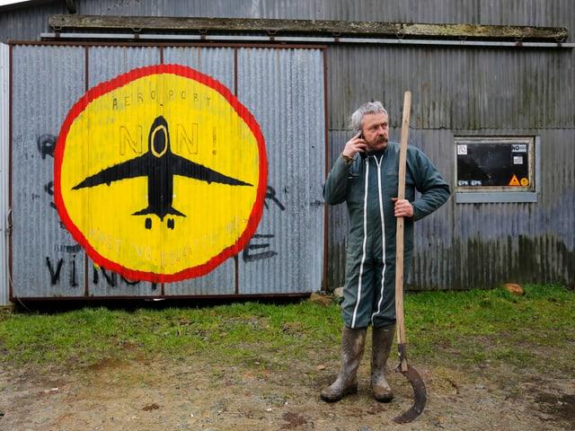 Ein Bauer mit einer Sichel und einem Handy am Ohr. Im Hintergrund ein Stoppschild mit einem Flugzeug drin auf eine Scheune gemalt.