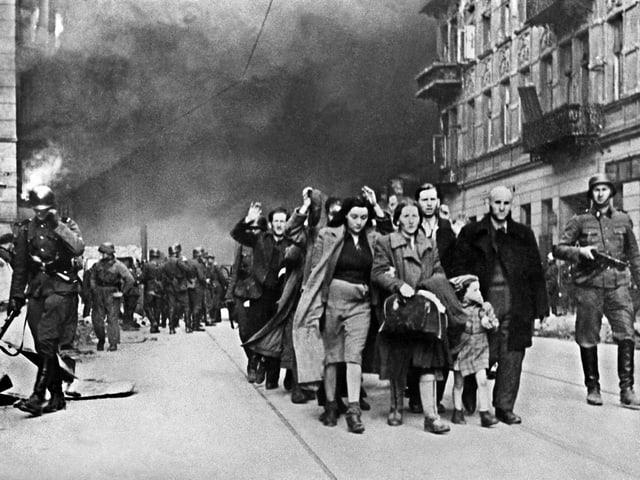 Schwarz-Weiss-Bild: Personen auf einer Strasse, die von einer Gruppe Soldaten begleitet wird.
