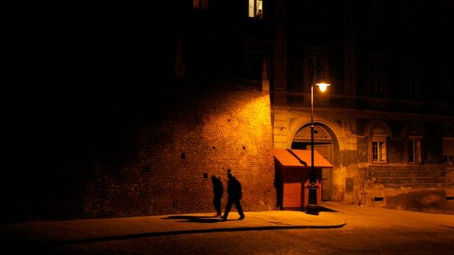 Eine spärlich beleuchtete Dorfstrasse in der NAcht, zwei Menschen gehen ihr nebeneinander entlang