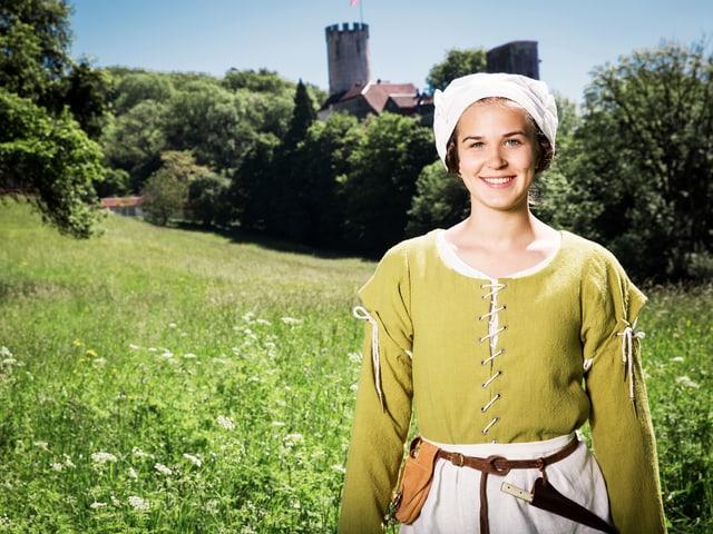 Junge Frau in mittelalterlicher Kleidung auf einer Wiese mit einer Burg im Hintergrund