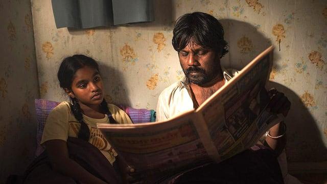 Ein Mann liest einem Mädchen aus einer Zeitung vor.