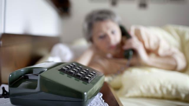 ein ältere Frau liegt im Bett und telefoniert