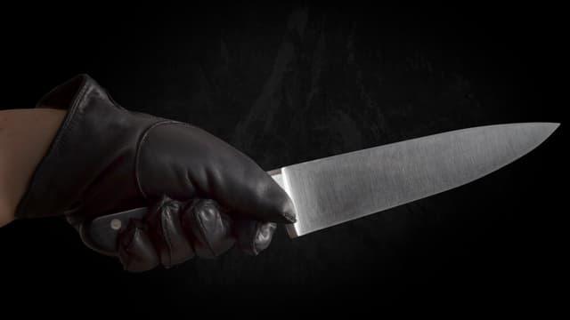 Hand mit Handschuh und Messer