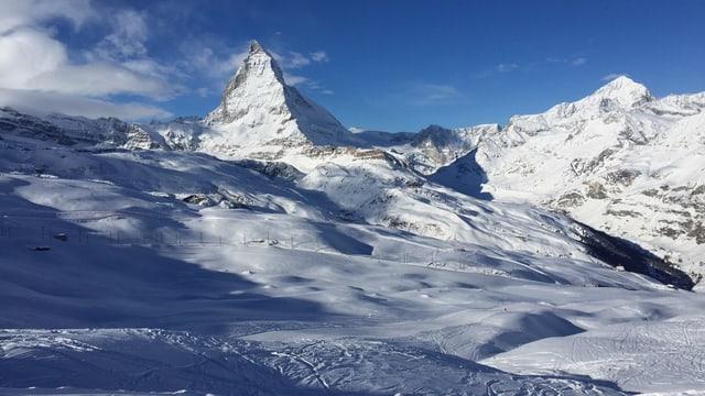 Matterhorn in der Ferne, davor schneebedeckte Hänge und Skispuren.