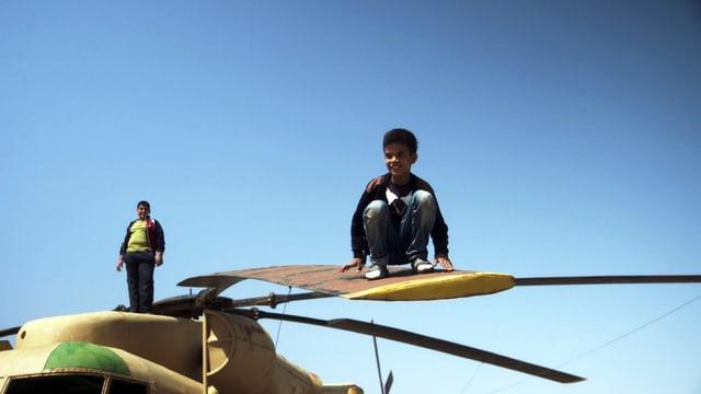 Kinder spielen mit dem amerikanischen Hubschrauber, der bei der gescheiterten Geiselbefreiungsaktion der USA im Iran zurückblieb.