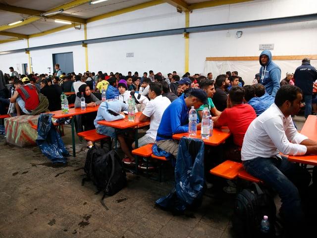 Flüchtlinge sitzen an langen Tischen im Erstaufnahmezentrum.