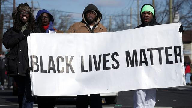 Vier Afroamerikaner demonstrieren mit einem weissen Plakat, auf dem steht: «Black Lives Matter».
