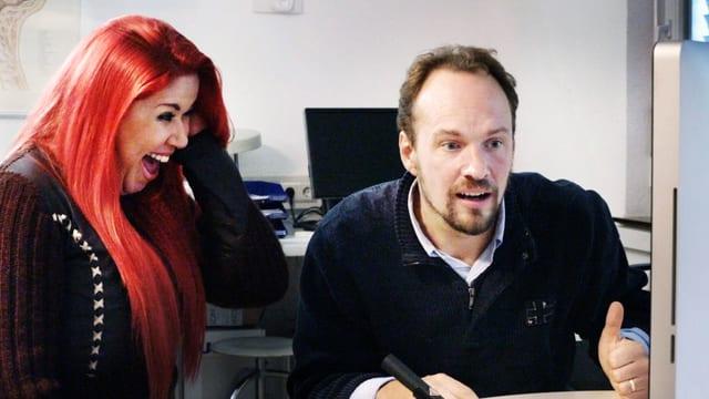 Eine Frau und ein Mann starren auf einen Bildschirm und schauen erstaunt