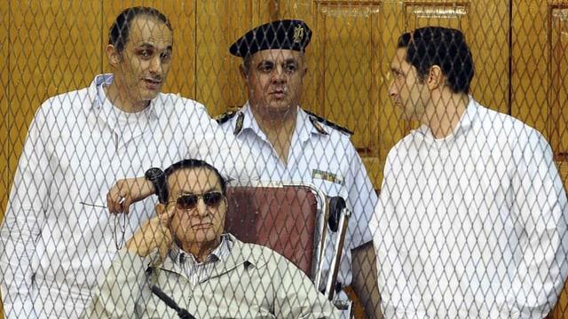 Husni Mubarak im Gerichtssaal, seine beiden Söhne an seiner Seite