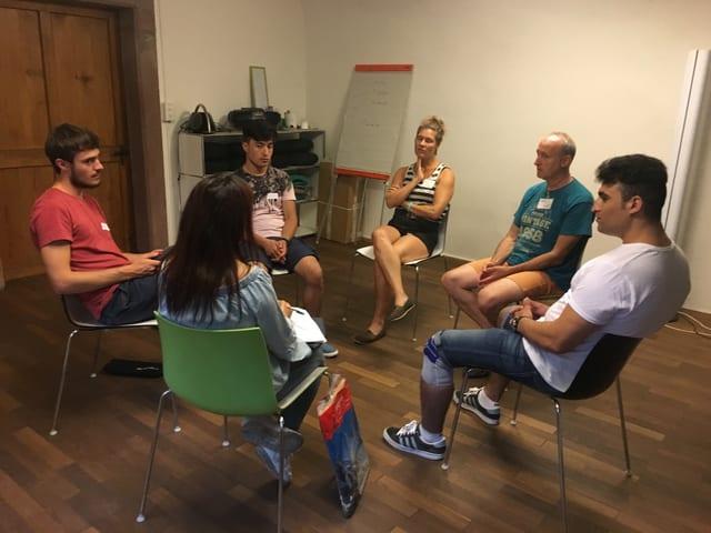 Sechs Leute sitzen im Kreis und sprechen miteinander